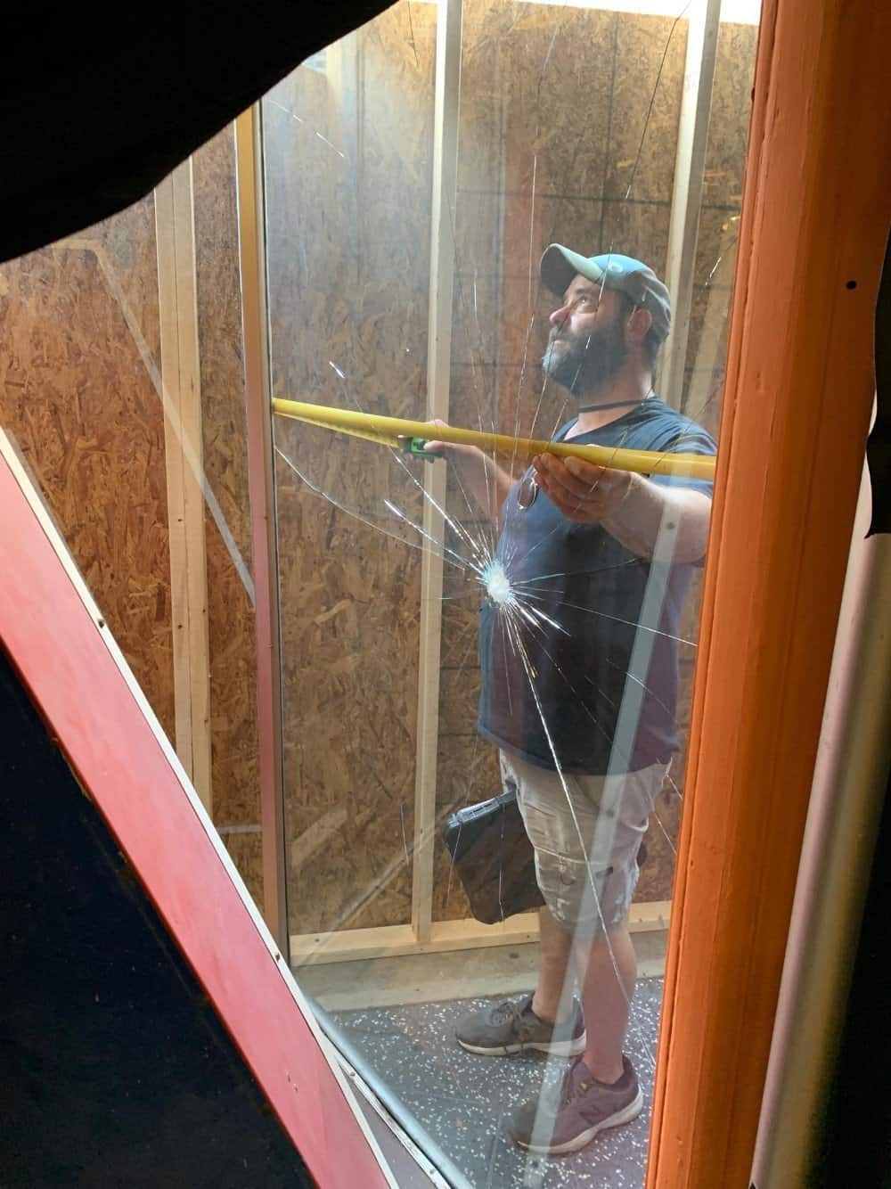 Owner Isaac Smith measuring for replacement storefront glass